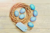 traditional eggs painted in blue color inside woven wooden wreath