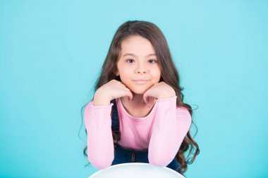 Child model smiling with long brunette hair, hairstyle