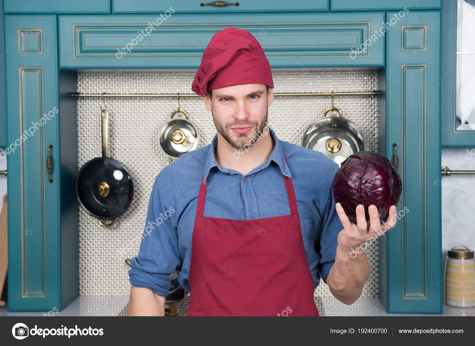 Cavolo viola della stretta dell uomo in cucina. Cuocere in cappello da chef  e grembiule. Vegetale e utensili da cucina per cucinare piatti. 511e99d9c6b8