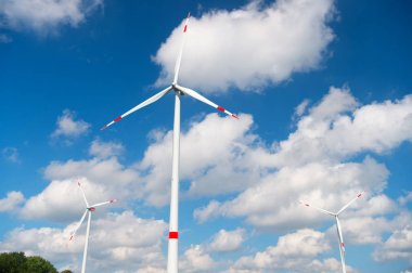 Wind turbine on cloudy blue sky. Alternative energy and electricity source. Global warming. climate change and ecology. Eco power and green technology concept