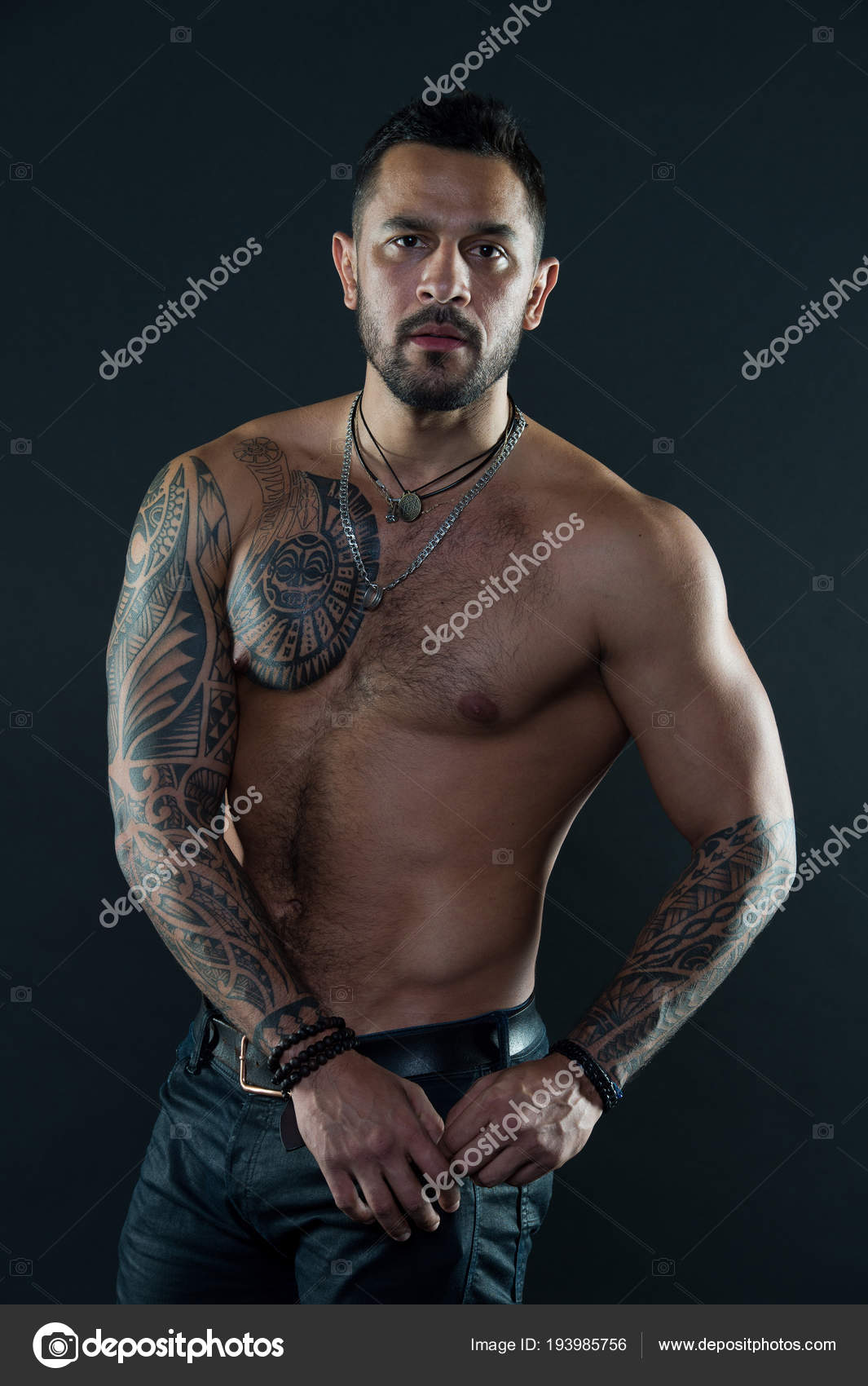 6c0499fa3 Bearded man with tattooed body. Macho with sexy bare torso in jeans. Tattoo  model with six pack and ab. Athlete or sportsman with muscular chest and  belly.