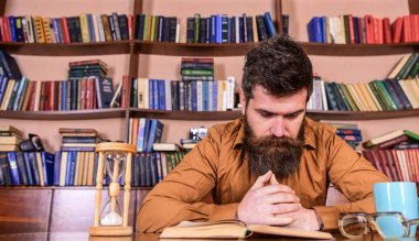 Man on concentrated face reading book, studying, bookshelves on background. Teacher or student with beard studying in library. Man sits at table with mug and hourglass. Self education concept
