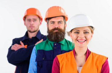 Woman and men in hard hats stand close as team.