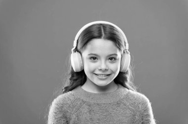 Music produces pleasure. Perfect sound stereo headphones. Girl cute little child wear headphones listen music. Kid listen music orange background. Recommended music based on initial interest