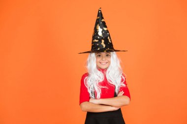 Looks perfect. trick or treat. supernatural charmer gray hair. kid enchantress orange background. happy halloween. magic fantasy. smiling girl halloween party. mystery witch. small child witch hat
