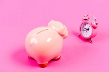 It is time to pay. Piggy bank pink pig and little alarm clock. Financial crisis. Economics and finance. Banking account. Bankruptcy and debt. Pay for debt. Bank collector service. Credit debt