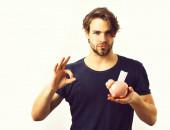 Kaukasische sexy junge Macho hält rosa Sparschwein