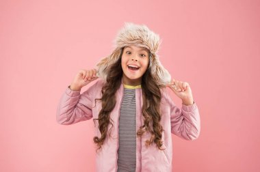 Warm smile. happy child pink background. warm clothes for cold season. kid fashion. trendy girl look like hipster. autumn style. Childhood activity. fur earflap hat accessory. small girl winter hat