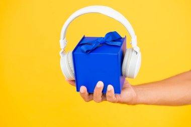 music gift conept. gift box with headphones. male hand hold present yellow backdrop. modern headset. what is inside. audio accessories sale. christmas music gift. musical present. convenient delivery