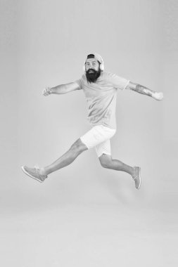 Energetic and upbeat music for leisure. Energetic hipster jumping high on yellow background. Bearded man in mid air. Brutal guy enjoying energetic music. Active and energetic