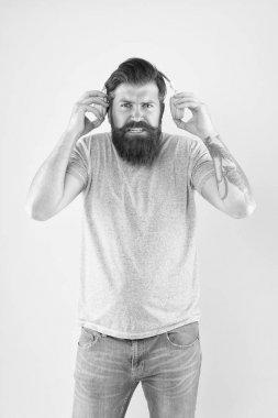 Hateful song. Music taste. Bearded guy dislike music. Irritating sound. Man listening music wireless headphones. Equalizer settings. Awful sound. Hipster listen broken headphones music gadget