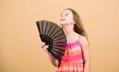 Fotografie Kühlung und Belüftung. Sommerhitze. Frische Luft. Mädchen fächelt sich mit Fächer auf. Aufbereitungsanlage. Klimakontrolle. Klimaanlage. winken, um aktuelle Luft zu schaffen. kleines Mädchen schwenkt eleganten Fächer