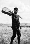 Moment spielen. Cowboy-Mann mit Akustik-Gitarrist. sexy Mann mit Gitarre im karierten Hemd. Hipster-Mode. glücklich und frei. Countrymusik. Westerncamping und Wandern