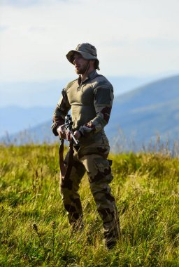 Focus and concentration experienced hunter. Ready to shoot. Army forces. Man military clothes with weapon. Brutal warrior. Rifle for hunting. Hunter hold rifle. Hunter mountains landscape background