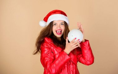 Little Christmas magic. morning before xmas. winter holidays and vacation. woman in down jacket. girl santa hat. padded coat fashion. warm clothing. fun and gifts. happy new year. merry christmas