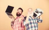 Digitale Technologien. Kampf der Technologien. Alte Generation. Männer arbeiten mit Schreibgeräten. modernes Leben und Überreste der Vergangenheit. Senior mit Schreibmaschine und Hipster mit Laptop. Neue Technologien beherrschen