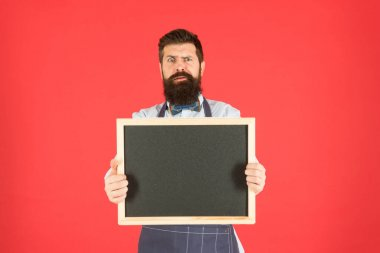 Time for dinner. brutal waiter in kitchen. mature man red backdrop. scared hipster bartender. What to cook. Restaurant menu. cafe shop advertisement. bearded man chalkboard, copy space. Dont like it