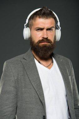 Lifestyle music fan. Man listening music wireless headphones. Hipster use headphones gadget. Inspiring song. Music library. Bearded guy enjoy music. Audio book. Application for listening books