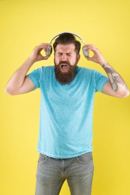 Modern music genre. Bearded man listen and sing to modern song. Modern hipster wear stylish headphones. Using modern technology for pleasure. Fun and entertainment