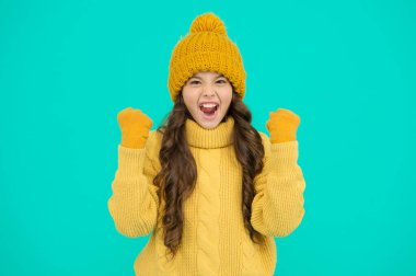 Happy winter holidays. homemade knit. cold season fashion. keep yourself warm. small girl in favorite sweater. hat and gloves accessory. happy child turquoise wall. no flu. ready for winter holiday