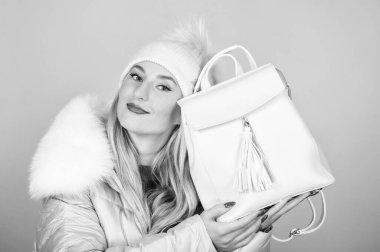 what is inside. girl in puffed coat. faux fur fashion. flu and cold season. Leather bag fashion. warm winter clothing. shopping. happy winter holidays. woman in beanie hat with backpack