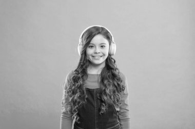 Let the music take you away. Cute little child listening to music playing in stereo headphones. Adorable girl enjoying music on blue background. Music education for small children