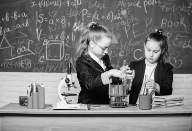 Genius kids work on own chemical theory. Basic knowledge of chemistry. Pupils cute girls use test tubes with liquids. Chemical experiment concept. Safety measures for providing safe chemical reaction
