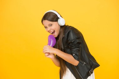 Recording studio. Beautiful voice. Developing voice. Voice synthesis will change the way music distribution works. Small girl listening music headphones. Musical education. Singing hairbrush mic