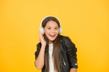 Music trends shaping future. Musical taste. Musical accessory. Gadget shop. Small girl listening music wireless headphones. Stereo sound. Musical education. Perception of sounds. Learning lyrics
