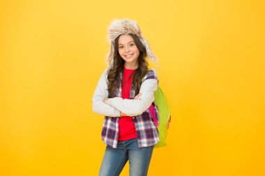 winter events at school. small girl wear earflap hat. winter school time and holidays. back to school. schoolgirl backpack yellow background. no classes this week. cheerful child pupil