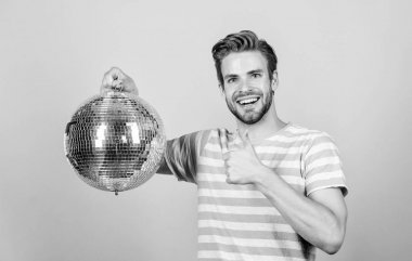 Cheerful dj man. How about party. Handsome man hold disco ball. Disco dances night club. Retro music. Guy inviting you at party. Thousand tiny mirrors reflecting lights creating disco atmosphere