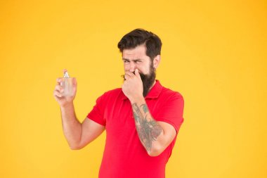ugly smell. hygiene and health. bearded man hold perfume bottle. perfect aroma for real men. brutal hipster choose smell. mature man recommended deodorant. Fashion cologne bottle. dont like it