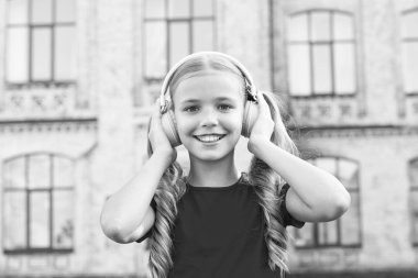 Expand opportunities. Inspired by music. Girl listening music modern gadget. Cute kid with wireless headset. Stereo headphones. Adorable kid using modern technology. Modern child. Perfect sound