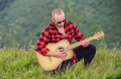 Musik ist, was ich bin. Countrymusik. sexy Mann mit Gitarre im karierten Hemd. Hipster-Mode. Westerncamping und Wandern. glücklich und frei. Cowboy-Mann mit Akustikgitarrist