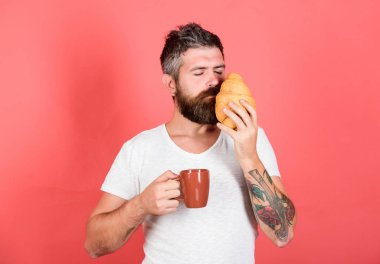 like it. Delicious breakfast. Unhealthy but yummy breakfast. Perfect match. feel hunger. Bearded hipster enjoy breakfast drink coffee. Morning tradition concept. Fresh baked croissant