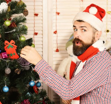 Guy in hat and scarf stands by fir tree. Festivals and decor concept. Santa Claus with surprised face on red holiday garlands background. Man with beard decorates Christmas tree stock vector