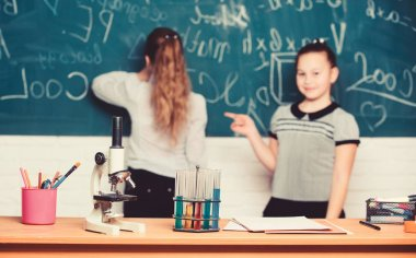 Chemical reactions. Make studying chemistry interesting. Pupil at chalkboard on chemistry lesson. Educational experiment concept. Girls classmates study chemistry. Microscope and test tubes on table