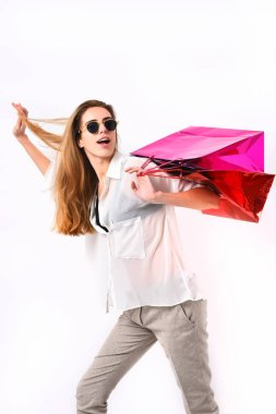 Lady holds red and pink shopping bags.