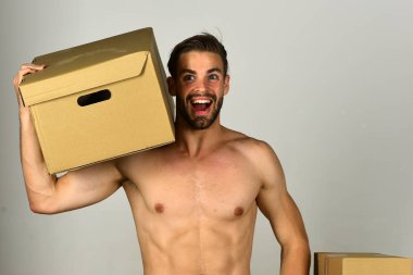 Macho with beard and surprised face carrying box