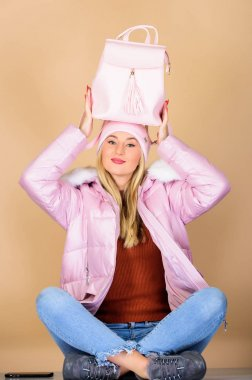 favorite bag. flu and cold season. Leather bag fashion. happy winter holidays. warm winter clothing. shopping. woman in beanie hat with backpack. girl in puffed coat. faux fur fashion