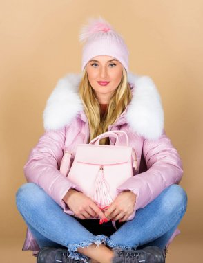 cold season. woman in beanie hat with backpack. warm winter clothing. shopping. girl in puffed coat. faux fur fashion. flu and cold season. Leather bag fashion. happy winter holidays