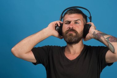 Dj with beard wears headphones. Music, party and leisure concept.