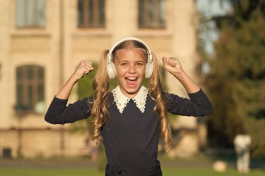 Adorable kid using modern technology. Modern child. Perfect sound. Expand opportunities. Inspired by music. Girl listening music modern gadget. Cute kid with wireless headset. Stereo headphones