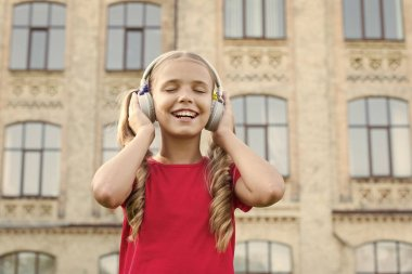 Future famous singer. Inspired by music. Girl listening music modern gadget. Cute kid with wireless headset. Stereo headphones. Adorable kid using modern technology. Modern child. Perfect sound