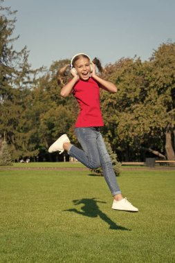 Never ending joy. Girl listening music modern gadget. Kid happy with wireless headset dancing running jumping. Stereo headphones. Kid using modern technology. Modern child. Perfect loud sound