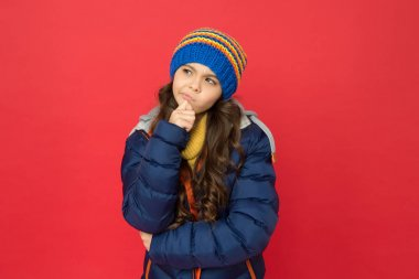 Winter dreaming. thoughtful child in warm winter clothes. seasonal fashion for kids. small beauty red background. little girl puffer jacket and knitted hat. care yourself in cold weather