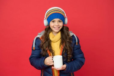 All I need is coffee and maybe music. Happy child hold coffee cup red background. Little girl enjoy drinking coffee. Hot drink. Winter cold. New technology. Modern life. Music and coffee make my day