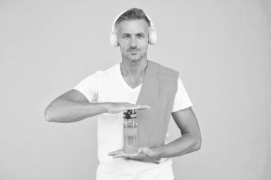 Drinking water is key to reaching fitness goals. Healthy drinking habits. Handsome man in headphones hold bottle of drinking water. Drinking water for better dehydration. Presenting and advertising