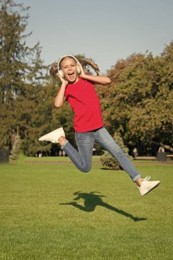 Perfect loud sound. Never ending joy. Girl listening music modern gadget. Kid happy with wireless headset dancing running jumping. Stereo headphones. Kid using modern technology. Modern child