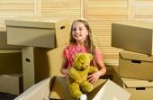 Vše ve tvém dosahu. šťastná holčička s hračkou. koupě nového bydlení. Kartónové krabice - stěhování do nového domu. Šťastná dětská lepenková krabice. Dojemný koncept. nový byt